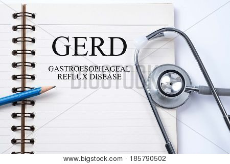 Stethoscope on notebook and pencil with GERD (Gastroesophageal Reflux Disease) words as medical concept.