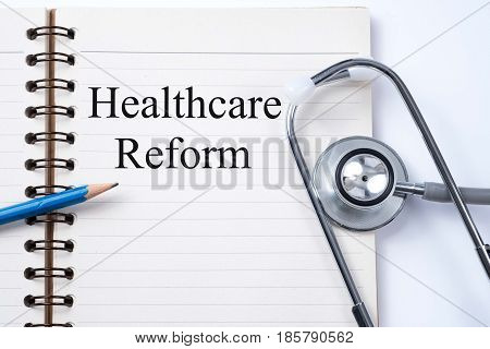 Stethoscope on notebook and pencil with healthcare reform words as medical concept