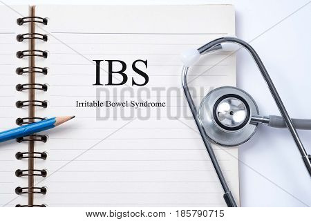 Notebook and pencil with IBS (Irritable Bowel Syndrome) on the table with stethoscope medical concept
