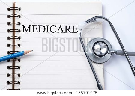 Notebook and pencil with Medicare on the table with stethoscope medical concept