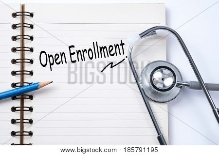Stethoscope on notebook and pencil with open enrollment words as medical concept