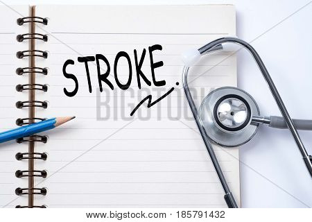 Stethoscope on notebook and pencil with stroke words as medical concept