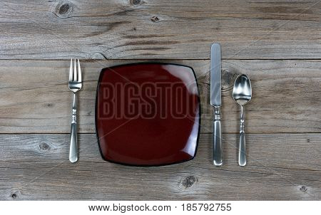 Plate with silverware on rustic wooden table in flat lay view
