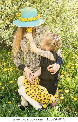Girl sits on hands at mother and gives her a sniff bouquet of dandelions
