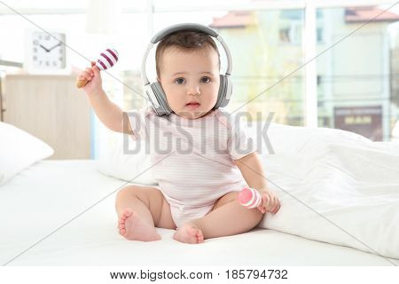 Cute little baby with headphones and rattles at home