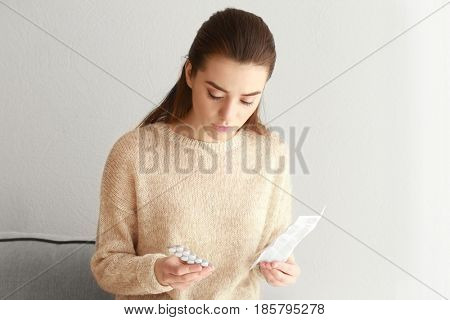 Beautiful young woman with pills and instruction at home