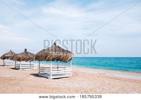 Summer arbors on beach. Breathtaking view on mediterranean sea. White wooden summerhouses on sunny day. Blue sky and fluffy clouds
