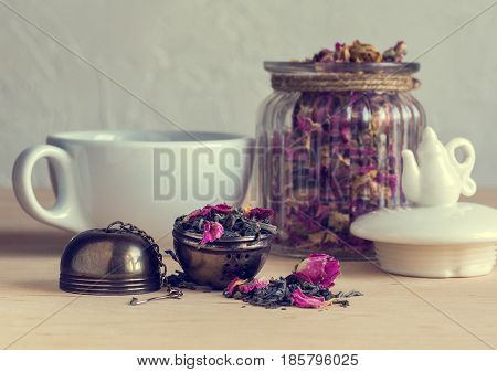 Tea strainer close-up tea leaves and pink buds on the background of a glass jar and cup selective focus retro style