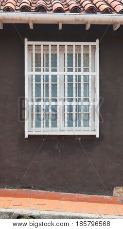 White wooden window on a wall brown background with red tile roof in vertical format
