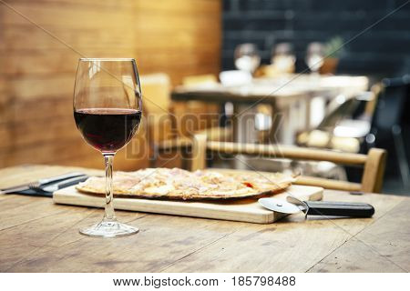 Traditional ham and brie cheese pizza with glass of red wine on rustic table