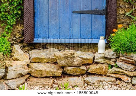 Entrance To A Country House, Blue Door, Milk Bottle In Front Of The Entrance, Stone House