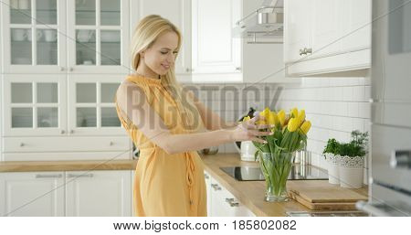 Wonderful young woman in romantic dress composing bouquet of yellow tulips while standing in light modern kitchen.