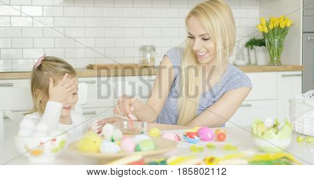 Laughing young mother and little adorable girl coloring Easter eggs together while sitting at table in kitchen.