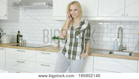 Young blonde standing with hand in pocket and smiling while talking by phone in modern kitchen.