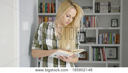 Young beautiful woman in checkered shirt concentrated on reading on background of shelves with books at home.