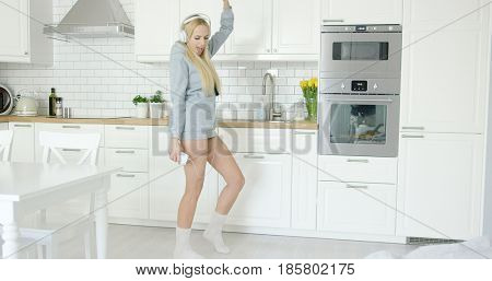 Young girl in sweat shirt listening to music in headphones and dancing in light modern kitchen alone.