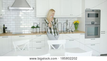 Lovely young female in home clothing standing in light modern kitchen alone and talking smart phone.