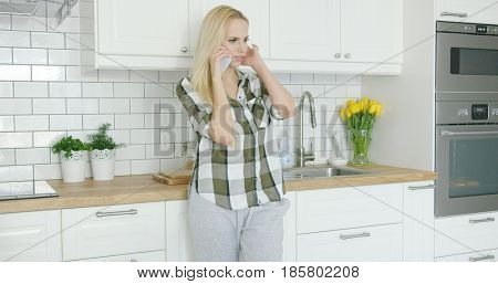 Beautiful young female in shirt and pants talking by phone in light and modern kitchen.