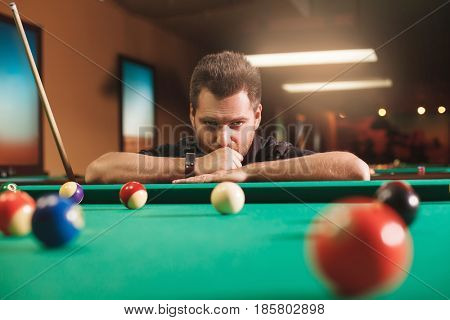 Thoughtful man plays billiards. Billiard room on the background.