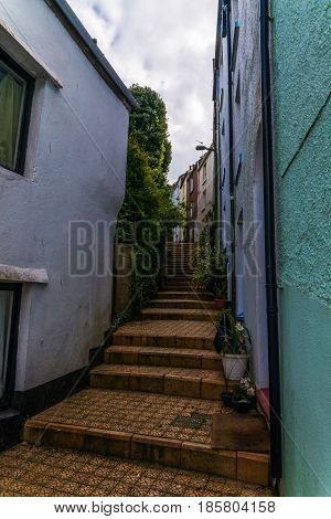 Narrow Passage From The Back Of Buildings In Seaside Town, Old Architecture, Stone Walls, Historic B
