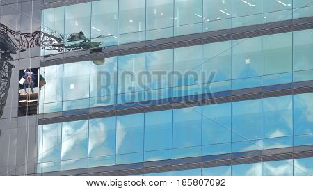 Workers cleaning the glass windows of a modern building with reflection sky and construction crane. Background in horizontal format