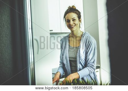 Cute lovely young woman standing and washing dishes at home.