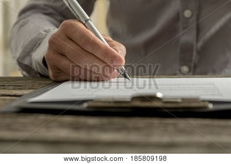 Closeup of male hand signing business contract or document with fountain pen on textured old rustic wooden desk.