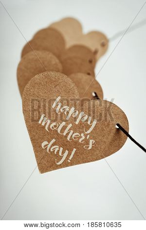 closeup of some brown cardboard hearts strung on a string and the text happy mothers day written in the first one, against an off-white background