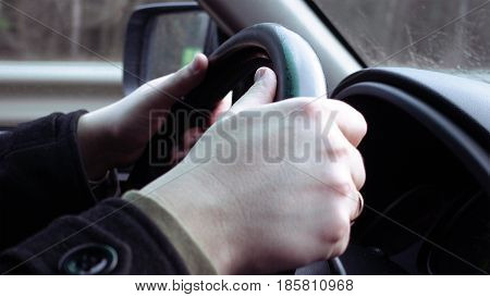 Driver's hands on the steering wheel closeup. Highway and urban traffic and driving scene.