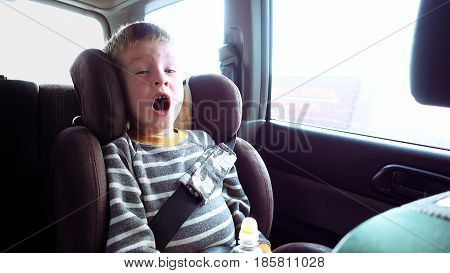 Little cute boy in a car seat looks out the window and yawns. Pure emotions over child face.