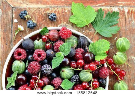 Garden berries in a bowl on wooden background. Top view.