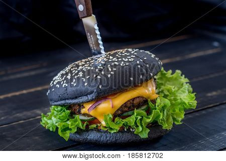 Black Burger with meat and cheese on a black wooden background