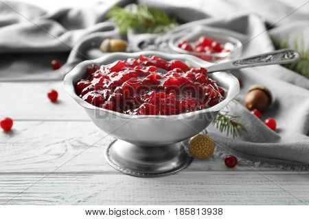 Delicious cranberry sauce in metallic  bowl on wooden background
