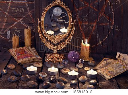 Magic ritual with ancient runes, mirror, tarot cards and candles. Halloween background, black magic rite or spell, occult and esoteric objects on witch table