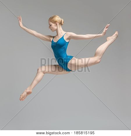Charming ballerina posing in the jump on the gray background in the studio. She wears a blue leotard. Her legs and arms stretched to the sides. Shoot from the side. Vertical.