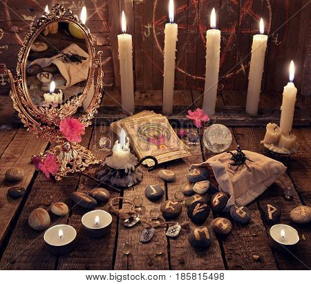 Mystic ritual with burning candles, magic mirror, flowers and the tarot cards. Halloween background, black magic rite or spell, occult and esoteric objects on witch table