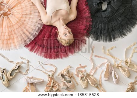 Delightful ballerina lies on the colorful tutus on the white floor in the studio. She wears a light top. Below her there are many pointe shoes. Tutus are peach, burgundy and black. Closeup.