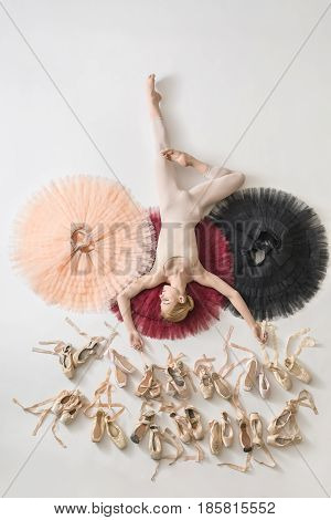 Ballerina with closed eyes lies on the colorful tutus on the white floor in the studio. She wears light dance wear. Below her there are many pointe shoes. Tutus are peach, burgundy and black.