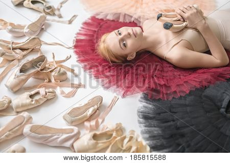 Attractive ballerina lies on the colorful tutus on the white floor in the studio. She wears a light top and holds pointe shoes. On the left there are many ballet shoes. Closeup. Horizontal.