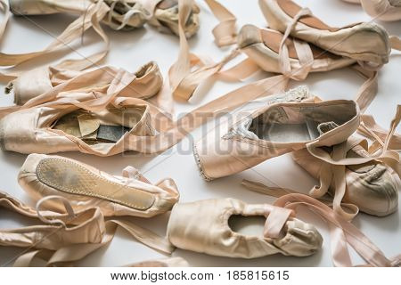 Lot of beige ballet shoes on the light floor in the studio. Closeup low aperture photo. Horizontal.