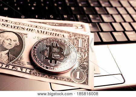 Bitcoin On Dollar Bill Over Laptop