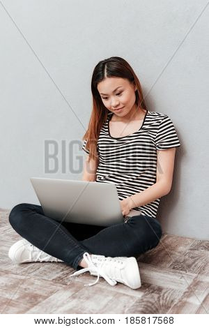 Hardworking woman working with laptop while sitting on floor isolated over grey