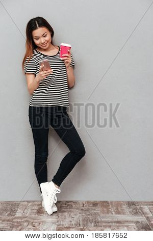 Image of happy young pretty woman standing over grey wall. Looking aside chatting by phone and drinking coffee.