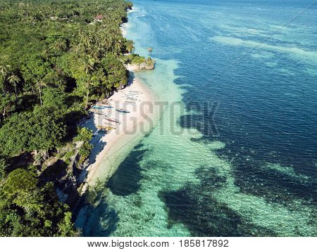 Aerial view of coast, turquoise sea, white sand beach with bangkas fishing boats. Bohol, Philippines 2016.