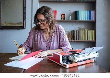 Portrait of a smiling mature woman journalist sitting at the table and making notes in notebook indoors