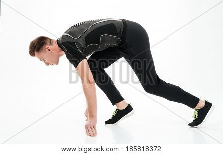 Side view portrait of a young concentrated sportsman ready to start running isolated over white background