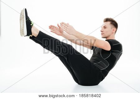Full length portrait of a young concentrated sportsman doing abdominal exercises on the floor isolated over white background