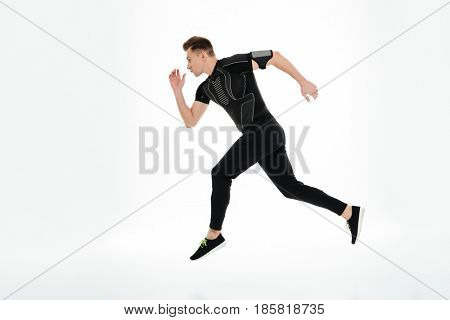 Side view full length portrait of a concentrated young sportsman started to run isolated over white background
