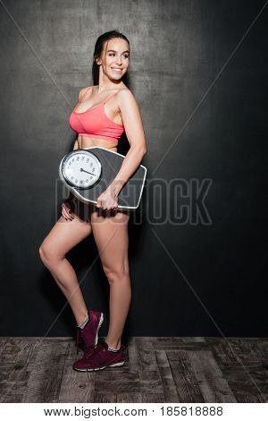 Cheerful brunette fitness woman holding weigher isolated over black