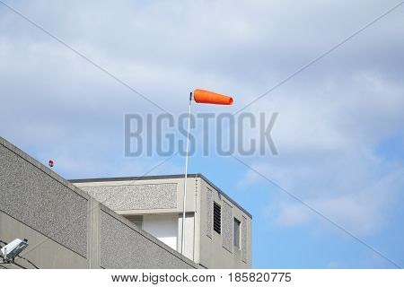 red windsock in the wind on top of the building